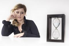 Secretary think the passing time watching an hourglass on the desk Stock Photos