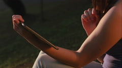 Hands of a woman its slide your photos in a park Stock Footage