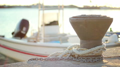 Bollard and boat in sunset - stock footage