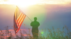 Soldier waves  American flag against   sunset sky. Slow motion scene Arkistovideo