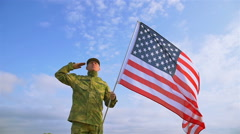 Soldier salute with  American flag against    blue sky. Slow motion scene Stock Footage