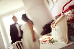 Beautiful bag on table. Groom and bride as silhouettes - stock photo