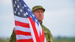 Soldier  stand  without movement  with  American flag .  Face close up .Slow mo Stock Footage