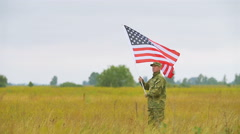Soldier  walk on field   with  American flag .  Slow motion scene Stock Footage