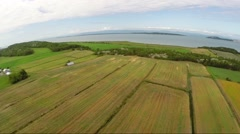 Aerial view over crop fields on St Lawrence River shoreline in Gaspe Peninsula Stock Footage