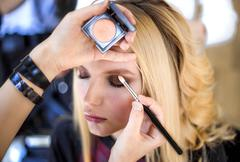 Make up artist applies cosmetics on models face Stock Photos