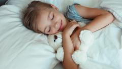 Portrait girl child sleeping with teddy bear in a bed and hugging toy. Top view - stock footage
