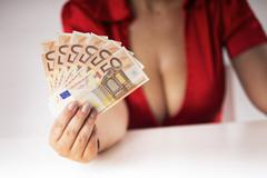 Girl with large breasts shows banknotes earned Stock Photos