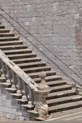Stone stairs along the high wall - stock photo