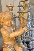 Antiques angel and candlesticks on flea market in Italy - stock photo
