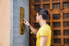 Young man ringing doorbell and talking on speaker phone - stock photo