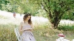 Youn woman read a book outdoor Arkistovideo