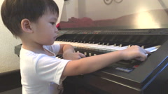 Asian boy learning to play electone - stock footage