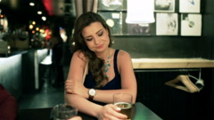 Uhappy woman sitting alone in the pub, steadycam shot Stock Footage