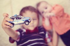 Boy holding a police car near baby brother - stock photo