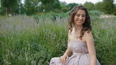 Young woman in long violet dress sit in lavender Stock Footage