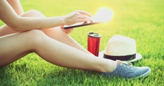 Woman using digital tablet computer sitting in the park, on a lawn. Slow motion Stock Footage