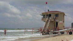 Lifeguard station with red flag in Tel-Aviv, people at the beach Stock Footage