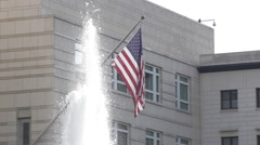 The US Embassy building with an American flag and fountain in Berlin Stock Footage