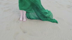 Beauty Girl in green dress stands on sand dune while wind blowing her clothes Stock Footage