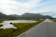 long strait road with ocean water on sides and mighty mountains in summer, ve - stock photo