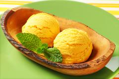 Stock Photo of Two scoops of yellow ice-cream in olive wood bowl