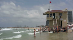 People in Mediterranean sea next to lifeguard tower on windy day, Tel-Aviv Stock Footage