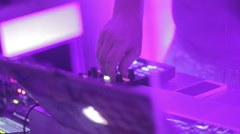 Male DJ hand turning controls on sound deck, playing soundtracks - stock footage