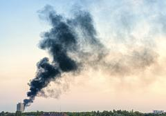 Plume of smoke from a fire above city at sunset. Stock Photos