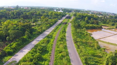 Aerial shot view railway with road on green filed Stock Footage