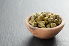 marinated capers in olive bowl on slate board with copy space - stock photo