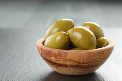 Pickled giant green olives in olive bowl on slate background Stock Photos