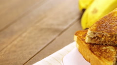 Stock Video Footage of Homemade peanut butter and banana  sandwich on white bread.