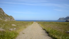 Long dirt road blue summer sky and ocean landscape Stock Footage