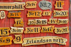 Collection of the wooden house numbers against the red wall. Stock Photos