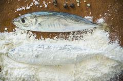 Floury fish on a wooden background Stock Photos