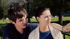 4k Happy couple talking and joking on park bench in summer - stock footage