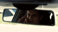 Man sits in the car. Reflection face in rearview mirror of car. Talking on phone Stock Footage