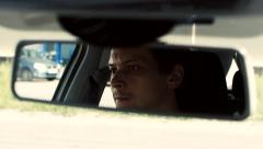 Man sits in the car. Reflection face in the rearview mirror of the car. Stock Footage