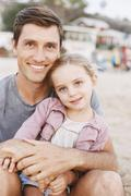 Young girl sitting on her father's lap, looking at camera, smiling. - stock photo