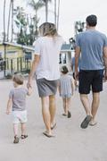 Rear view of a family, a couple walking with their young son and daughter. Stock Photos