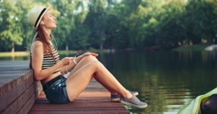 Attractive young woman listening to music sitting by the lake. Slow Motion, 4K. Stock Footage