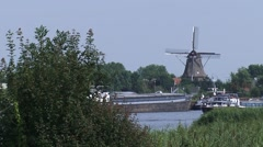 Yacht sailing on river Zwarte Water + skyline Windmill HASSELT, THE NETHERLANDS Stock Footage