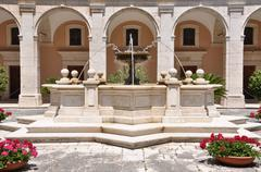 Stone water fountain against the building with arcades in the Monastery Stock Photos
