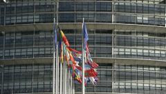 Panning to European Union country flags with European Parliament building in the Stock Footage