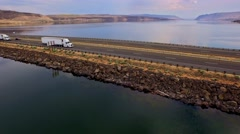 Truck crossing Columbia river with canyons in background Stock Footage