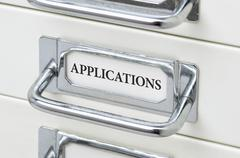 A drawer cabinet with the label Applications Stock Photos
