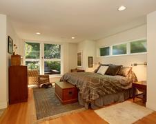 Luxury master bedroom with hardwood floor and brown bedding. Stock Photos