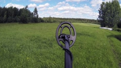 POV shot of metal detector being lowered down on grass at a hay field - stock footage