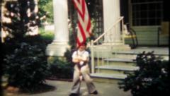 2420 patriotic boys wave flag in frontyard at home - vintage film home movie Stock Footage